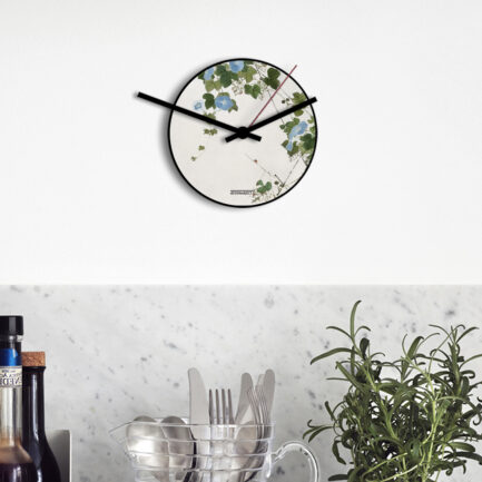 Small wall clock with blue flowers by designobject. This wall clock has three hands that come out of the dial and is a tribute to the Chinese painter Ju Lian